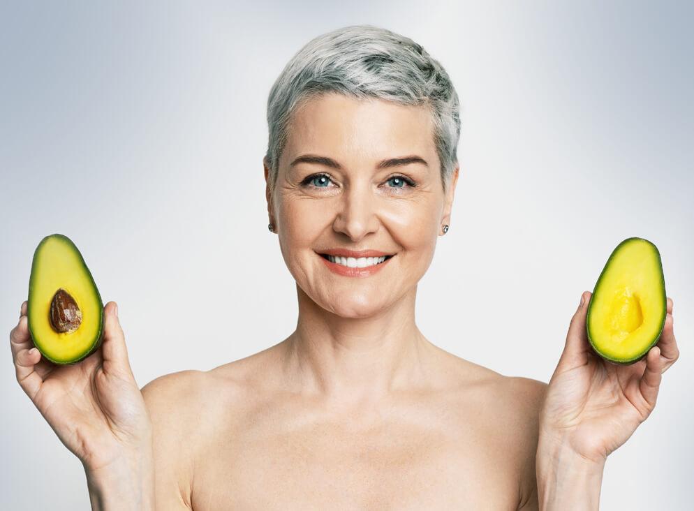 Grauhaarige Frau zeigt aufgeschnittene Avocado.
