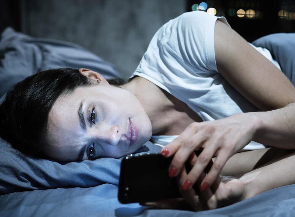 Frau liegt im Bett und liest auf Ihrem Handy.