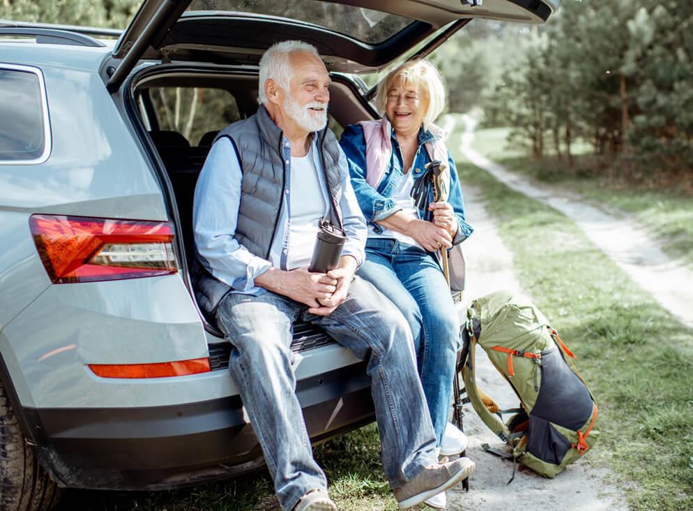 Älteres Paar sitzt im Kofferaum