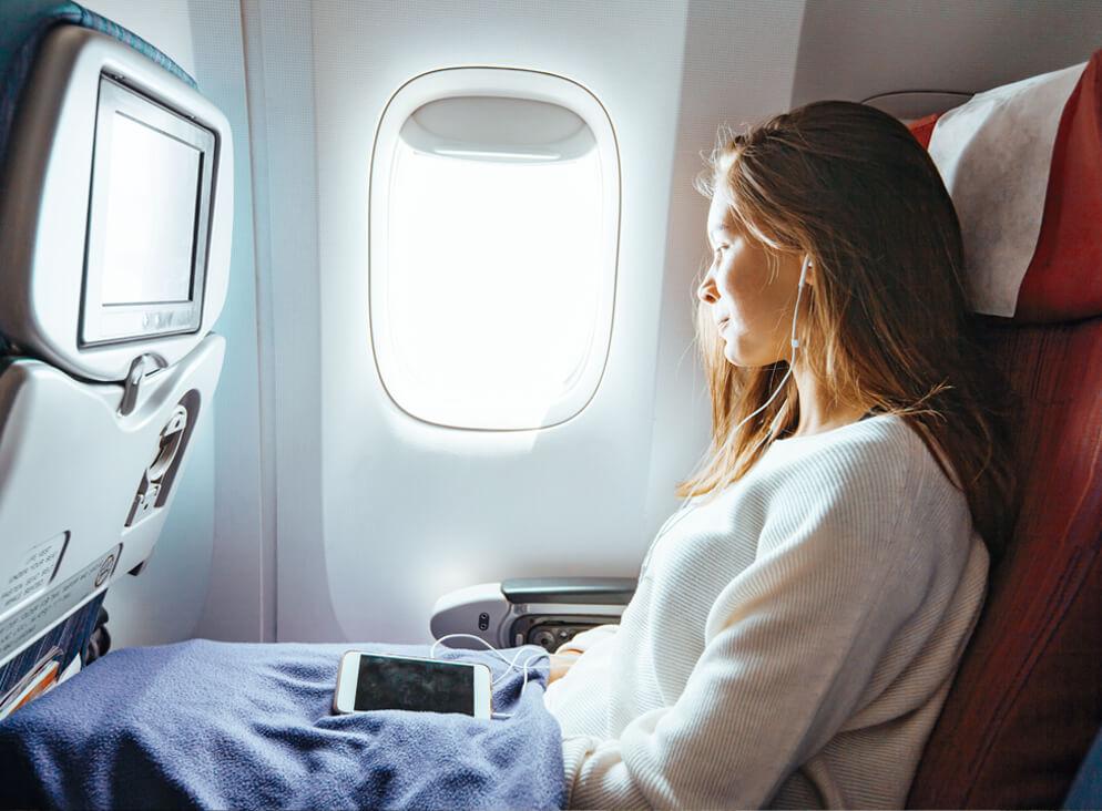 Junge Frau sitzt im Flugzeug